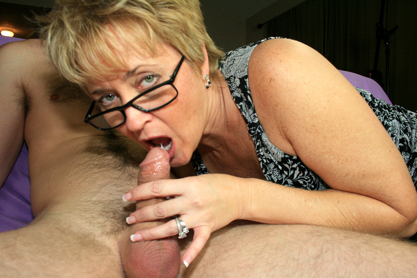 Free hd hot mature blonde with glasses is giving a young guy the best sex lesson ever porn photo